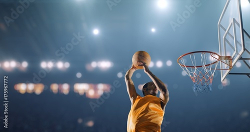 Fotobehang Basketbal Basketball player performs a slam dunk on a sport background