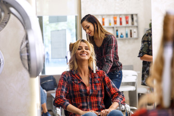 Working day inside the hair salon, hairdresser making hairstyle on blond woman