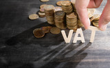 VAT wood word with stacked coins on dark wooden background, human's finger at T letter. - 175973156
