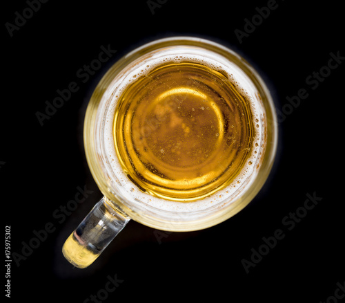 Top view of a glass of beer on black background
