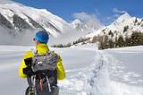 hiker  in the snow crossing alpine - 175977108