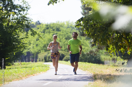 Poster Jogging Healthy, fit and sportive couple running in park