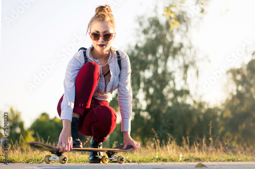 Fotobehang Skateboard Fashionable girl with a skateboard in the park