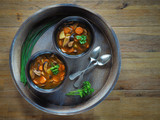 Mushroom soup in two brown bowls with spoons, parsley and chive on wooden tray. Overhead shot. - 175982719