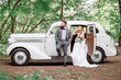 The bearded groom and beautiful bride. Retro car.