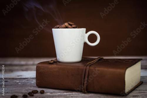 Poster Koffiebonen tazza di caffè fumante appoggiata su libro