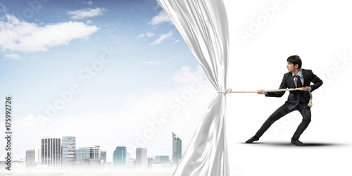 Young man opening white curtain and presenting modern city landscape