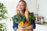 Beautiful young woman grocery shopping bag with vegetables at home. - 175992933