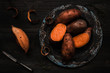 Raw sweet potato on the wooden black table top view