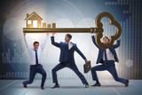 Businessmen holding giant key in real estate concept - 175996766