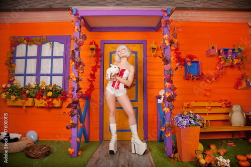 pretty futuristic halloween blonde lady with white cute rabbit outdoor near her orange house alone - 176000115