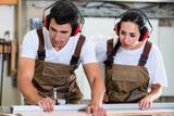 Tischler und Auszubildende arbeiten gemeinsam in Werkstatt - 176000516
