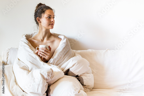 Póster Beautiful young woman covered by blanket is sitting on bed with hot tea