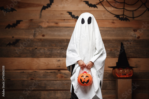 Leinwandbild Motiv Halloween Concept - little white ghost with halloween pumpkin candy jar doing trick or treat with curved pumpkins over bats and spider web on Wooden studio background.
