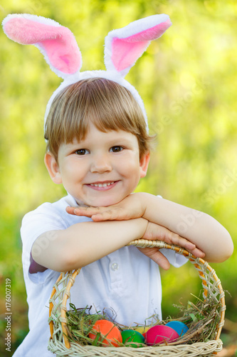 Easter bunny. Сhild with a basket of Easter colorful eggs. Kid, boy in a rabbit costume smiles.