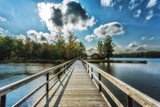 Picture of wooden bridge at the lake with blue dramatic clouds