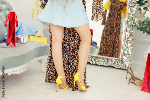 Girl trying on a dress in front of a mirror. Woman looks at purchases, fashionable clothes. Model with a leopard suit. Lady is going on a date, meeting