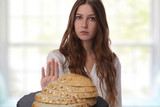 Gluten intolerance and diet concept. Teenage girl refuses to eat white bread. - 176016198