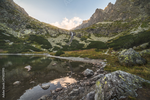 Foto op Canvas Bergen Mountain Lake with Waterfall and Rocks in Foreground at Sunset. Velicka Valley, High Tatra, Slovakia.
