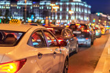 Fototapety taxi in traffic jam on the background of the lights of the night city and bokeh