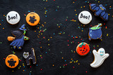 Bright halloween gingerbread cookies background with bat, witch, skeleton, ghost on black background top view copyspace - 176028544