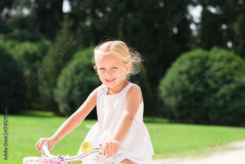 Happy child riding on her bike