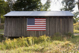 A weathered wood building and metal roof covering a bridge. The building is decorated with an American flag. Photographed in natural light.  - 176035787