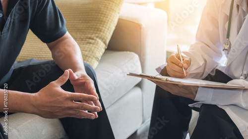 Leinwanddruck Bild Doctor consulting male patient, working on diagnostic examination on men's health disease or mental illness, while writing on prescription record information document in clinic or hospital office