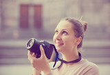 young woman holding camera in hands and photographing in   city - 176038175