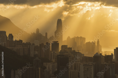 Silhouette of skyline of Hong Kong city with sun ray under sunset Poster