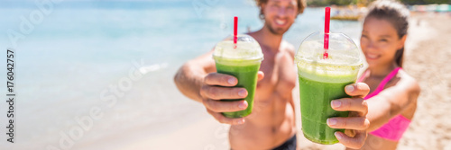 Spoed canvasdoek 2cm dik Sap Fitness couple drinking green smoothie at beach banner panoramic. Man and woman holding vegetable smoothies after running sport fitness training. Healthy clean eating lifestyle concept.
