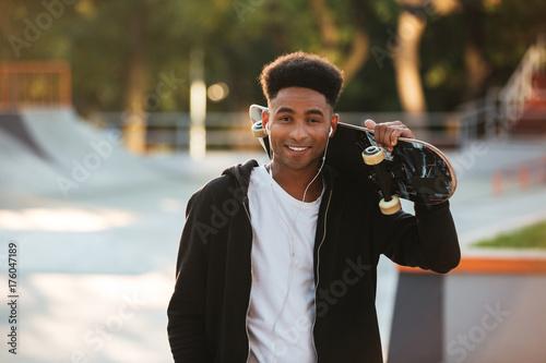 Fotobehang Skateboard Cheerful african teenager guy with earphones