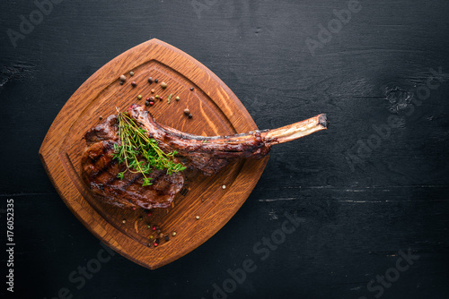 Papiers peints Steakhouse Steak on the bone. Top view. Free space for text. On a wooden background.