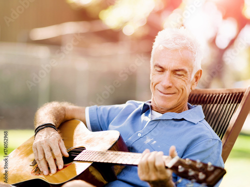 Senior man plying guitar outdoors Poster