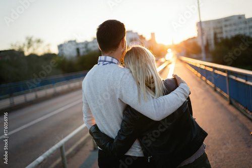 Poster Happy young attractive couple hugging on bridge