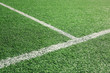 Artificial green soccer or rugby grass field with white intersection line. Selective focus used.