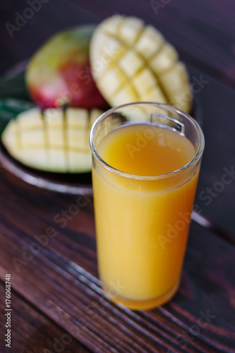 Staande foto Sap Fresh tropical mango juice on table with mango fruits on background.