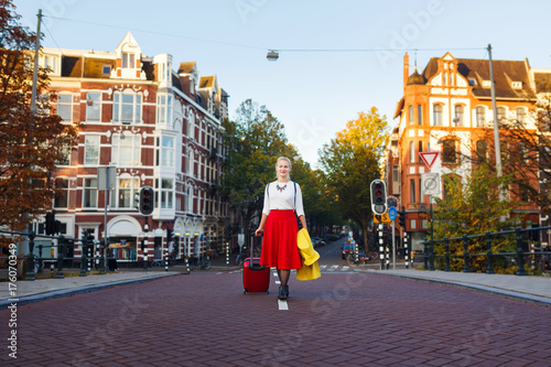 The woman with suitcase is walking in the street of Amsterdam city in autumn