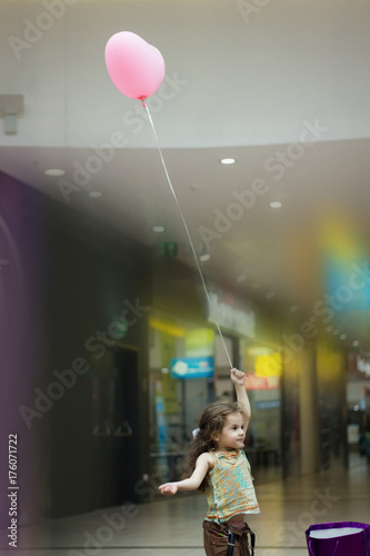 Little girl on inside the mall with the balloon in hand.