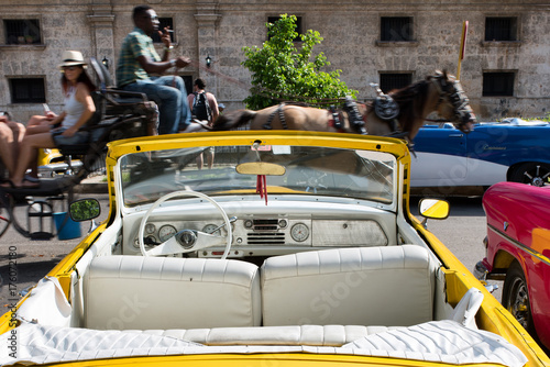 Poster Havana Vintage american yellow car parked and coach passing by in Havana Cuba