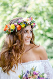 Beautiful bride in wedding dress with flower bouquet and wreast.