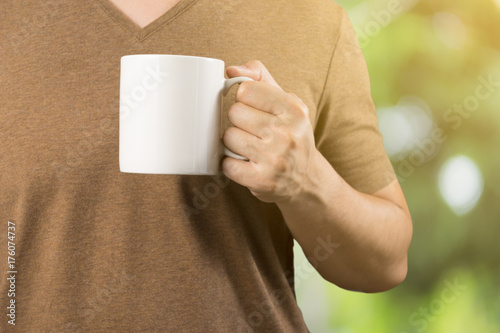 Asian man on Brown t-shirt Holding coffee cup .Relaxing ,feel good