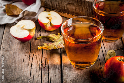 In de dag Sap Fresh organic farm apple juice in glasses with raw whole and sliced red apples, on old rustic wooden table, copy space
