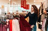 Brunette female customer selecting basic garments at the store. - 176076991