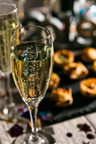 New Year: Glass Of Champagne With Party Food Behind - 176077536