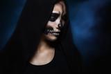 Halloween portrait of young beautiful girl in a black hood. skeleton makeup half face - 176091732