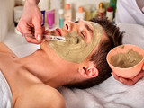 Mud facial mask of man in spa salon. Massage with clay full face. Girl on with therapy room. Healing clay for the face. Beautician with bowl therapeutic procedure isolated background. - 176095766