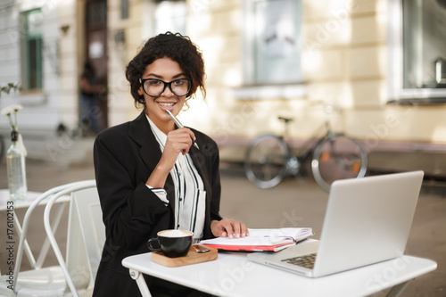 Portrait of African American girl sitting at the table of cafe and happily looking in camera with pen in hand. Pretty lady with dark curly hair in jacket working with cup of coffee and laptop on table