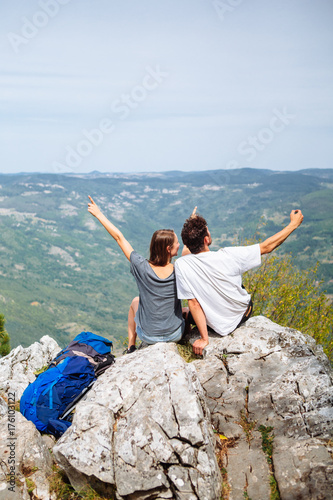 Young couple sitting on the rock and taking selfie Poster