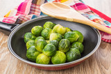 Frying pan with brussels sprouts, wooden spoon and napkin - 176109770